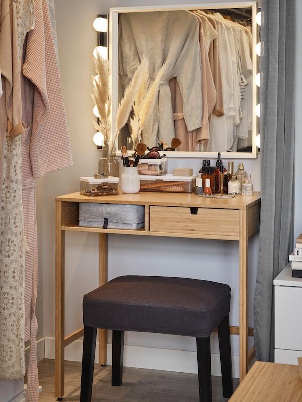 Toucador em bambu, com banco cinza escuro, e um espelho NISSEDAL branco com candeeiro LED de parede.cesto cinzento