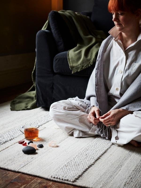 Žena sedí na svetlom koberci v obývacej izbe s krištáľmi, kameňmi a sklenenou šálkou pred sebou.