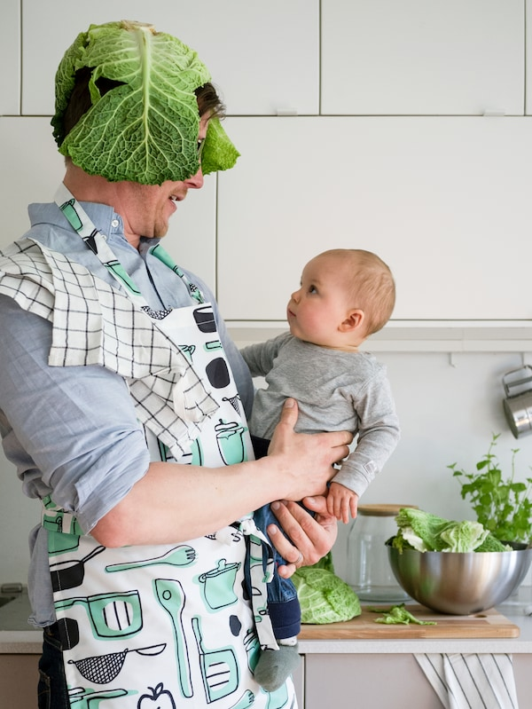 A man stands in a kitchen wearing a RINNIG apron and cabbage leaves on his head. He holds a baby who looks surprised.