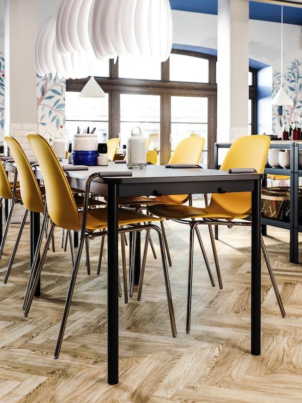 Sedie giallo scuro con braccioli appese a un tavolo color antracite, pavimento in legno, lampade a sospensione bianche.