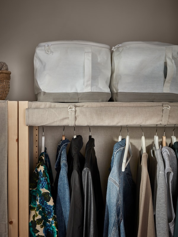 The top of an IVAR shelving unit with the cover rolled up, clothes on the hanging rail and LACKISAR storage cases.