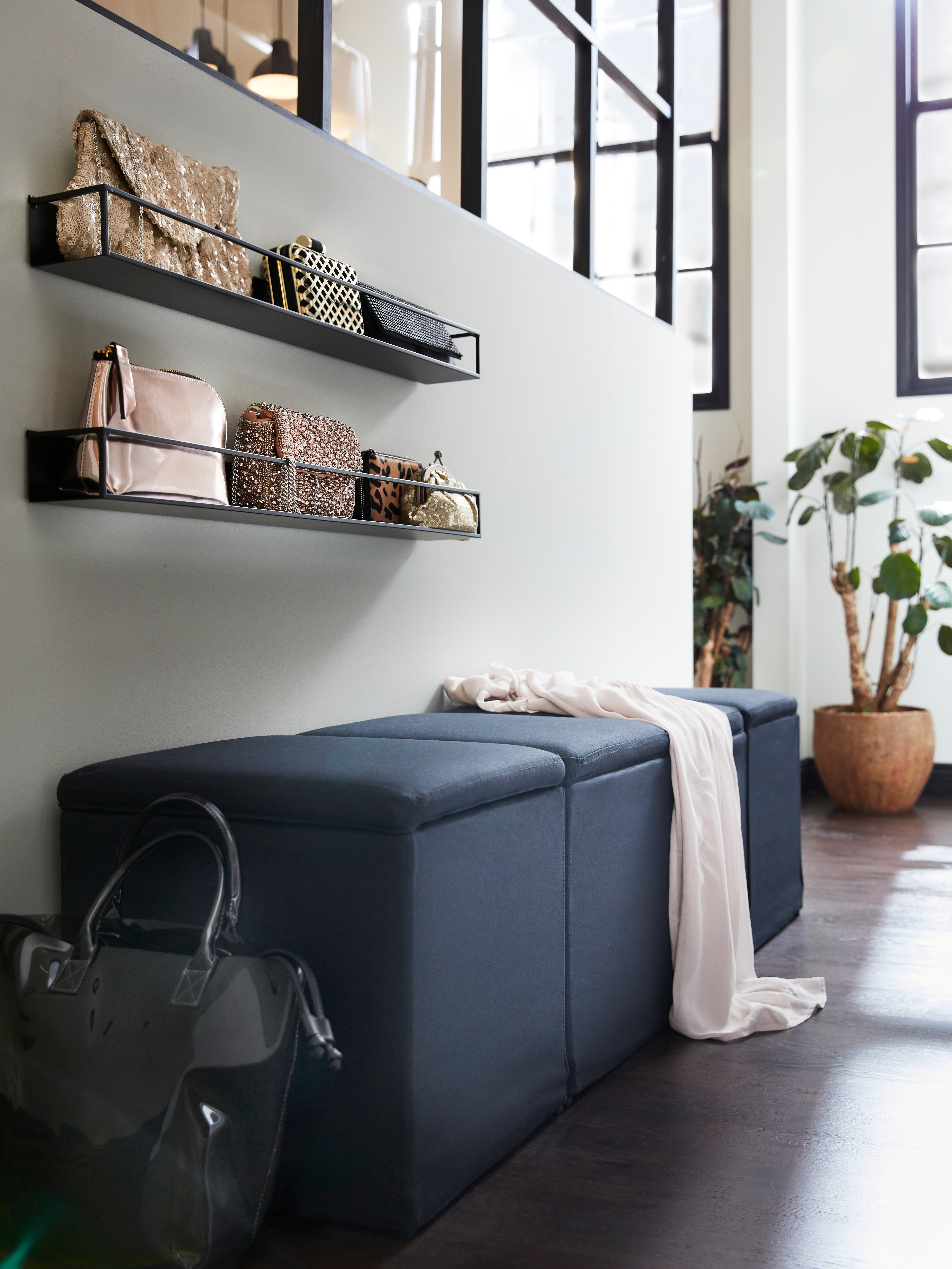 A row of cube-shaped, black BOSNÄS footstools with storage under the fabric seat against a wall that has purses on shelves.