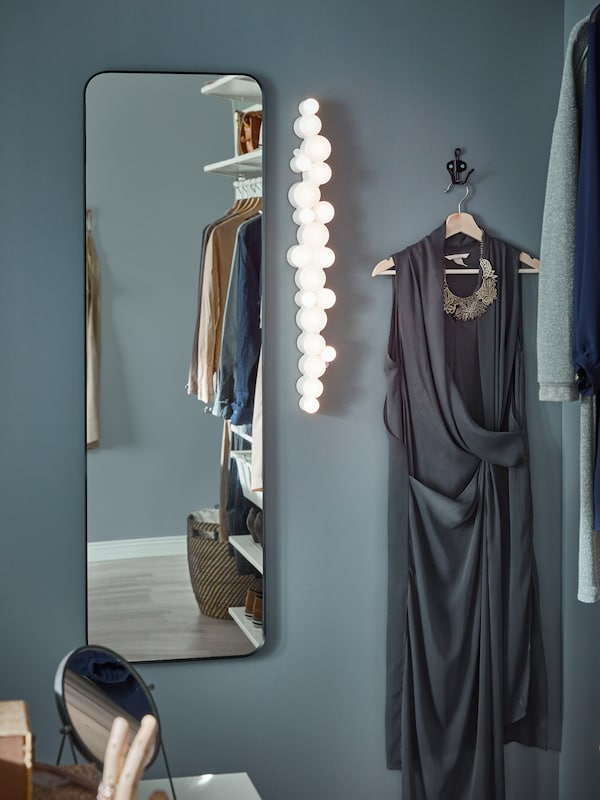 A full-length mirror on a blue-grey wall, a stylish lighting fixture, a black hook with a dark grey dress on a hanger.
