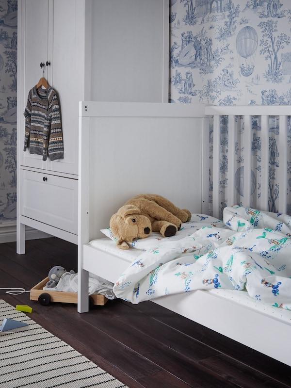 Hvid tremmeseng med hvide/mønstrede sengetekstiler og en blød tøjhund, trælegetøj på gulvet og et hvidt garderobeskab i baggrunden.