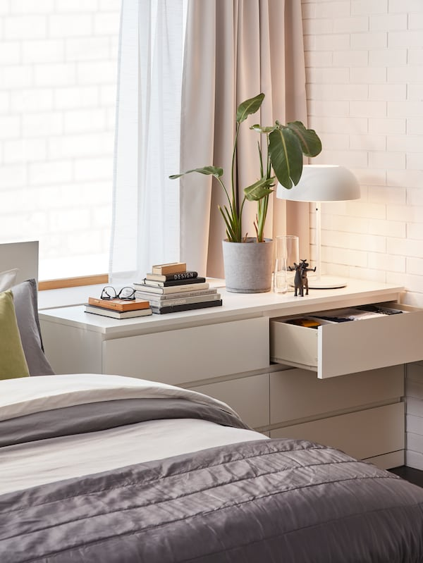 A white MALM chest of drawers with a comfy bed next to it and a plant, some books and a white NYMÅNE table lamp on top.
