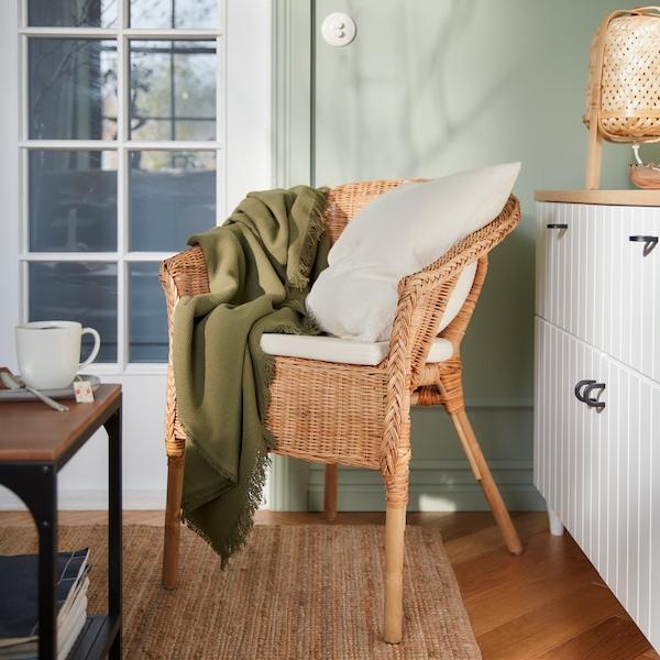 Rottinkinen AGEN-tuoli, jonka päällä on valkoinen VIGDIS-koristetyyny sekä vihreä ODDRUN-huopa. Lattialla on LOHALS-matto. Tuolin takana on BESTÅ-säilytyskokonaisuus, jonka päällä on KNIXHULT-pöytävalaisin.
