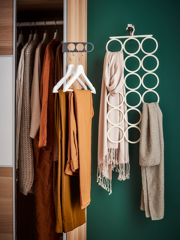 On the side of a PAX wardrobe, KOMPLEMENT valet and multi-use hangers hold neatly folded trousers and scarves, respectively.