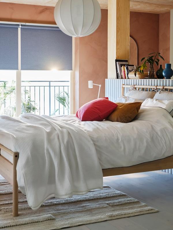 Un lit BJÖRKSNÄS est placé dans une chambre aux murs lambrissés alors que la lumière du soleil entre par la fenêtre de derrière.