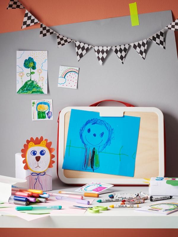 Különféle gyerekeknek készült művészeti és kézműveskedéshez szükséges eszközök egy asztalon.