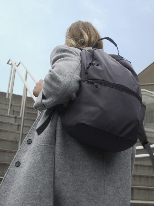 Une femme portant un sac à dos VÄRLDENS gris foncé et montant des escaliers en béton.
