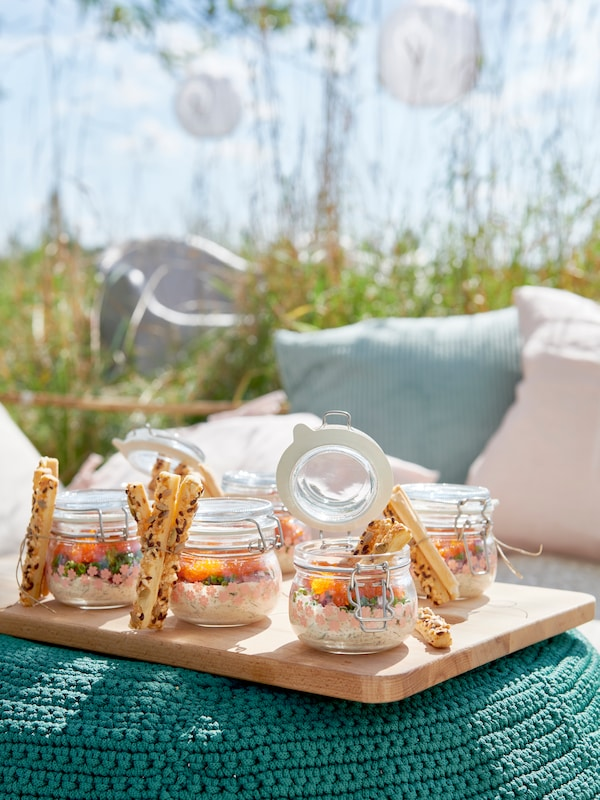 Glass containers filled with yogurt on top of a turquoise ottoman.