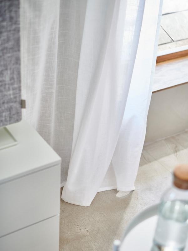Fehér SILVERLÖNN függöny és NORDLI fiókos szekrény részlet.
