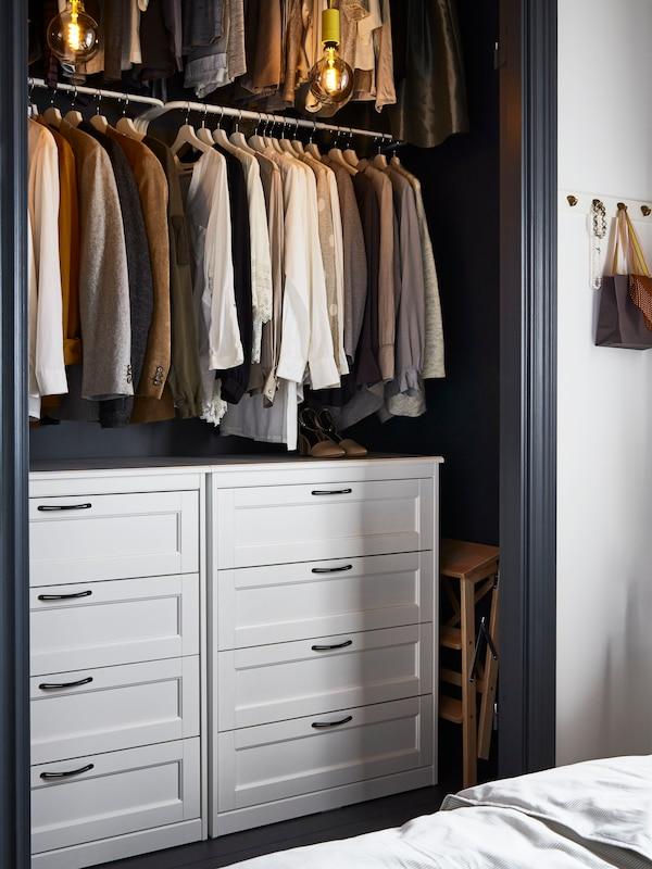 Vaatekaappi joka on koottu valkoisista SONGESAND-lipastoista ja MULIG-vaatetangoista.