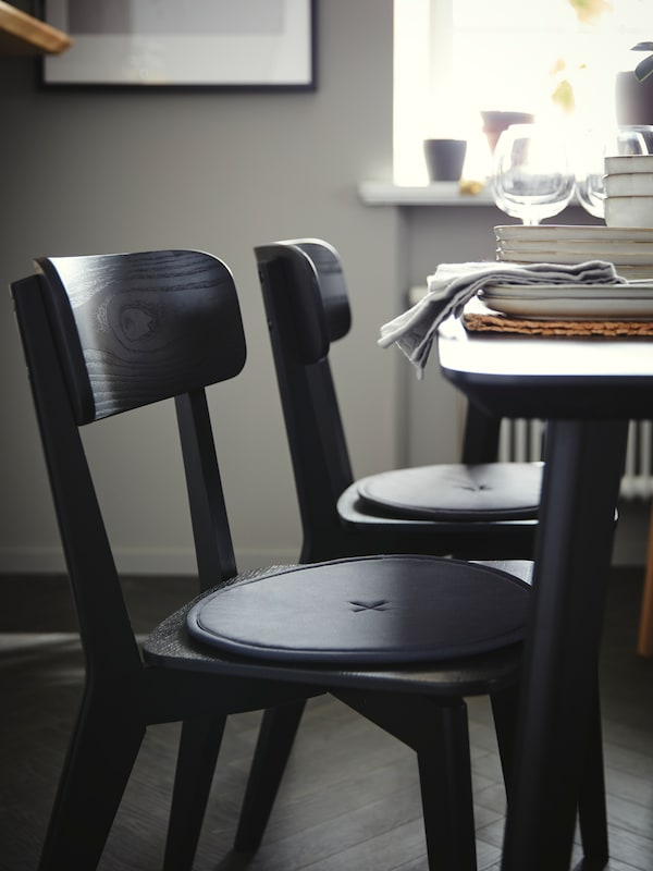 Two black LISABO chairs with STRÅFLY chair pads on each seat, at a LISABO dining table by a window with tableware on top.