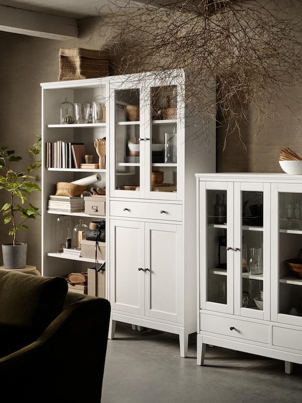 Rak buku berwarna putih, kabinet tinggi berpintu kaca dengan 1 laci berwarna putih, kabinet berpintu kaca yang boleh dilipat dua berwarna putih.