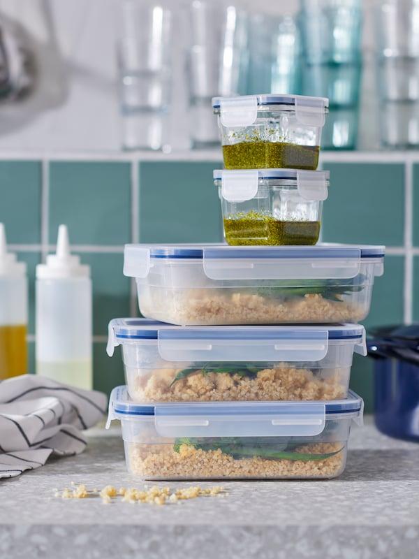 مجموعة من حافظات الطعام IKEA 365، كبيرة وصغيرة، مملوءة بالطعام وموضوعة وسط إكسسوارات مطبخ على سطح عمل.