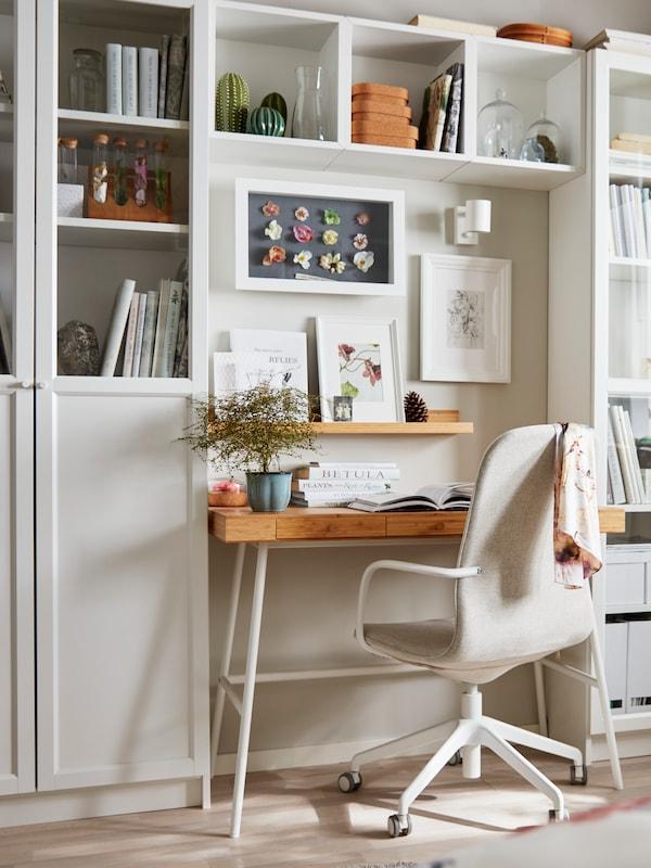 Et lille skrivebord i træ integreret i en hvid BILLY reol.