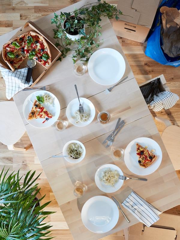 Matbord i bk´jörk dukat med vita tallrikar.