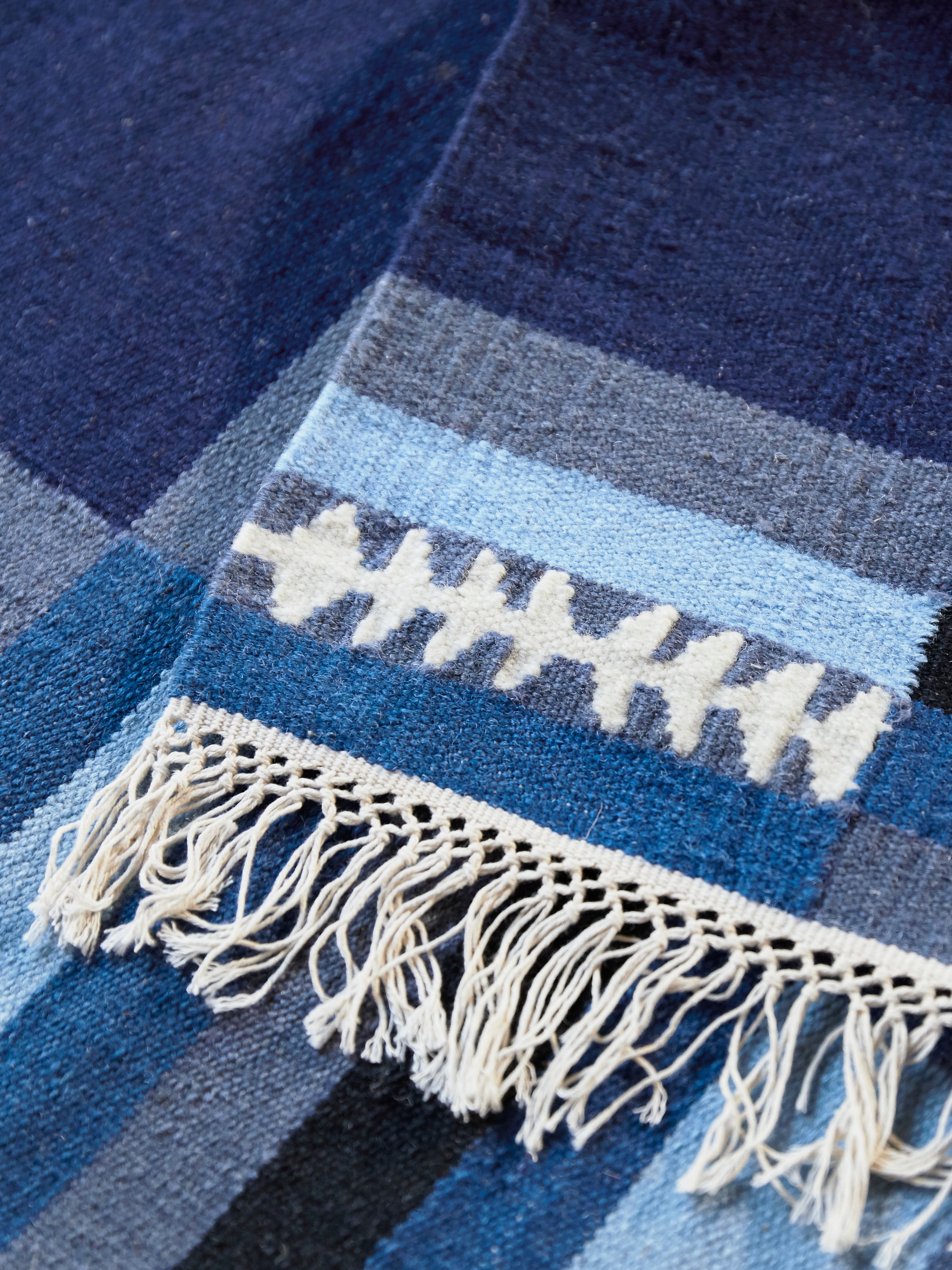 Dettaglio di un tappeto a tessitura piatta TRANGET in lana, con frange bianche e motivo a rettangoli in varie tonalità di blu.