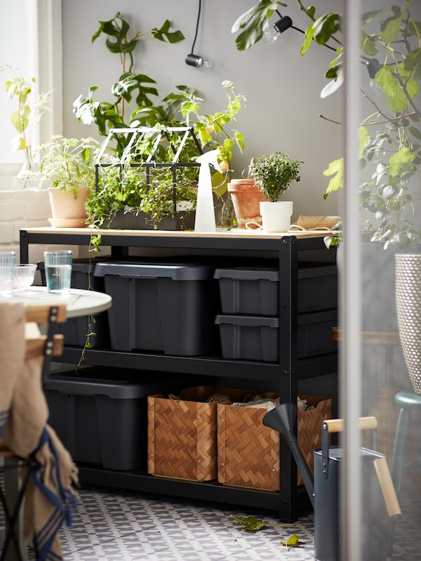 A work bench placed on a balcony, with plants on top and its shelves filled with neatly arranged, dark-grey KLÄMTARE boxes.