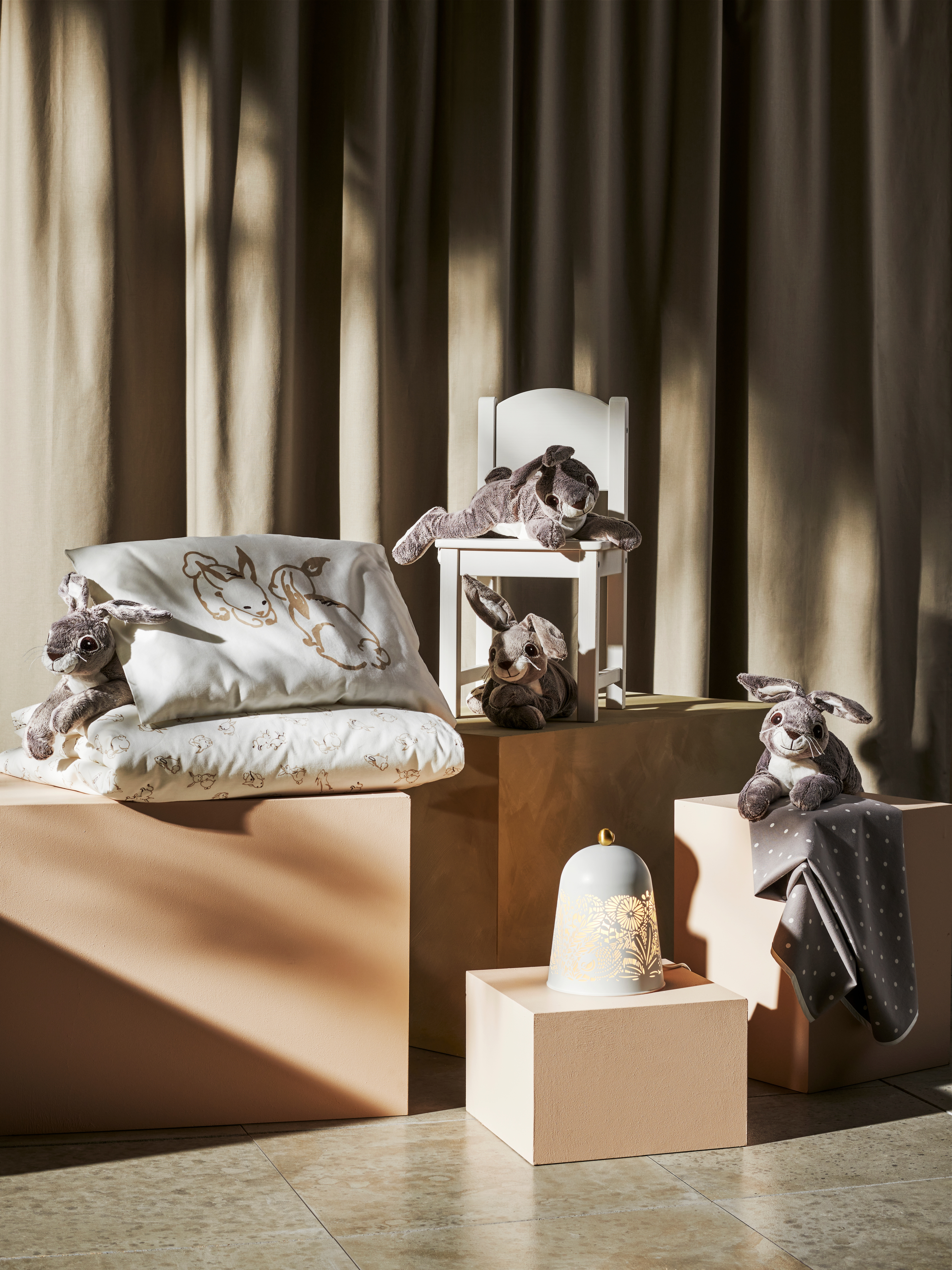 RÖDHAKE komplet posteljine, plišani zec, stolna lampa i podloga za bebe na postoljima, u pozadini su zavjese.