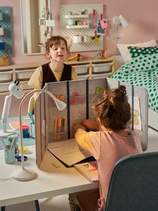 Két diáklány ül egymással szemben egy gyerekszobában, a két egymásnak tolt íróasztal között térelválasztó panel.