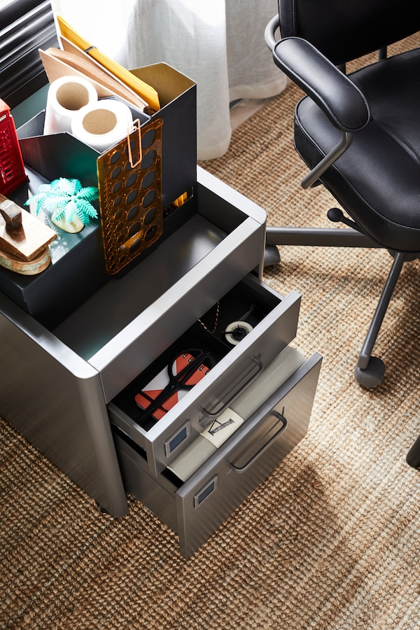 A dark gray IDÅSEN drawer unit on casters with a TJENA magazine file on top.