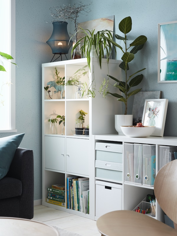 A white shelving unit with doors, potted plants, white storage boxes with lids, white magazine files, children's books.