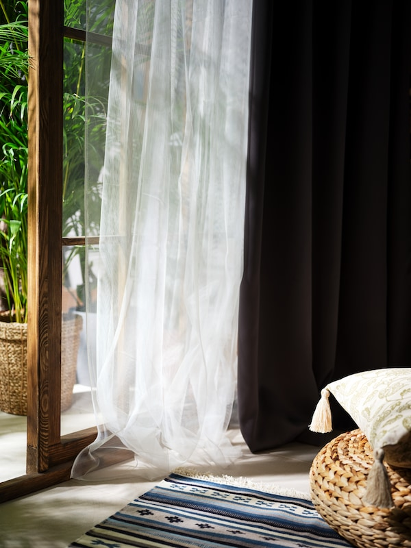 A combination of sheer, white curtains and grey HILLEBORG block-out curtains hanging next to an open glass door.