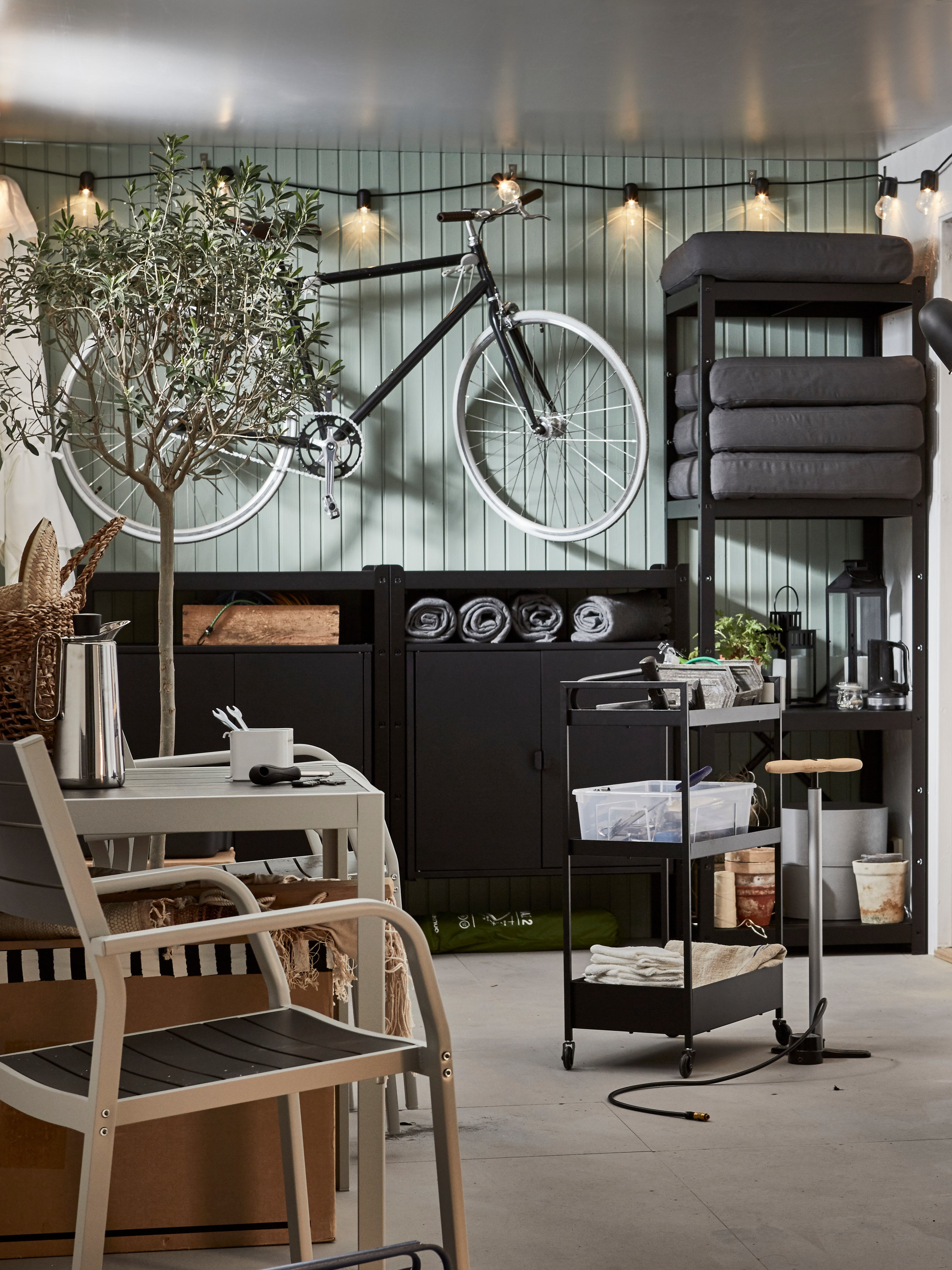A garage with bike, a lit lighting chain, a wall of storage, a seating area and a black NISSAFORS trolley holding tools.