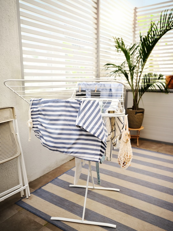 A white MULIG drying rack with clothes on a blue striped VRENSTED rug, a folded TORPARÖ chair and a big plant.