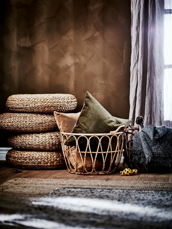 A basket filled with cushions, with a stack of footstools in the background.
