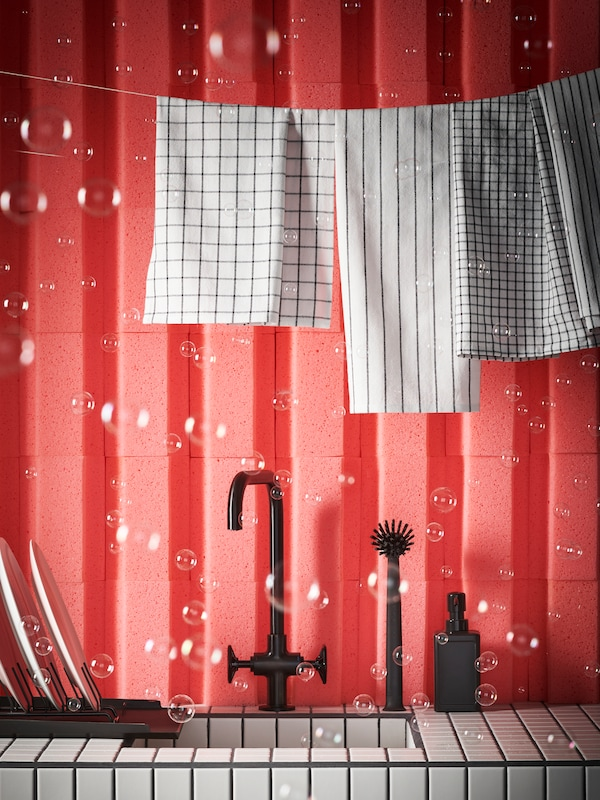 A line holding 4 RINNIG tea towels hanging across a sink with bubbles around it, and which has a black GAMLESJÖN mixer tap.