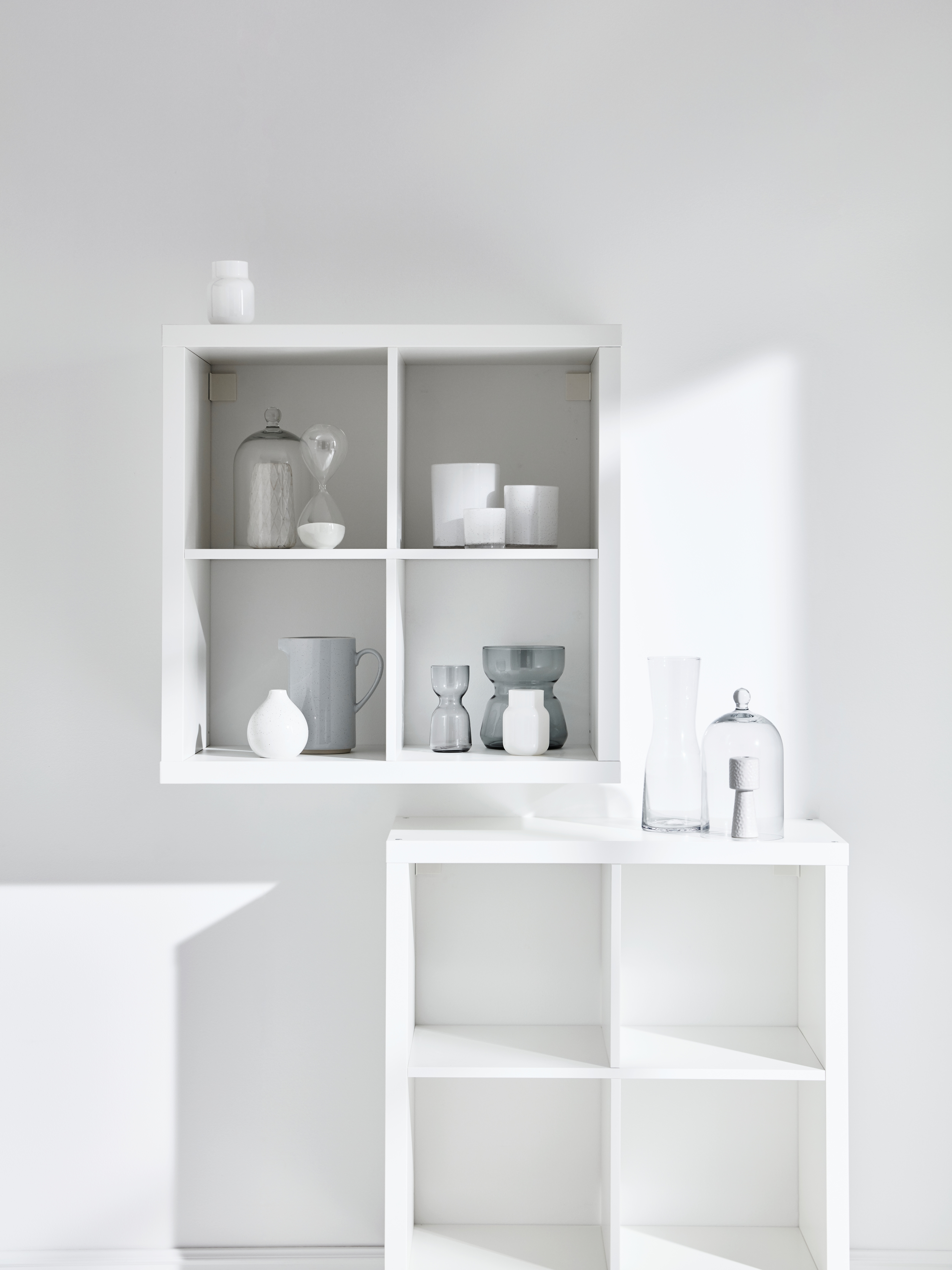 A cube-style, white KALLAX shelving unit is mounted on a wall, holding jars and pots. An identical, empty unit sits below.