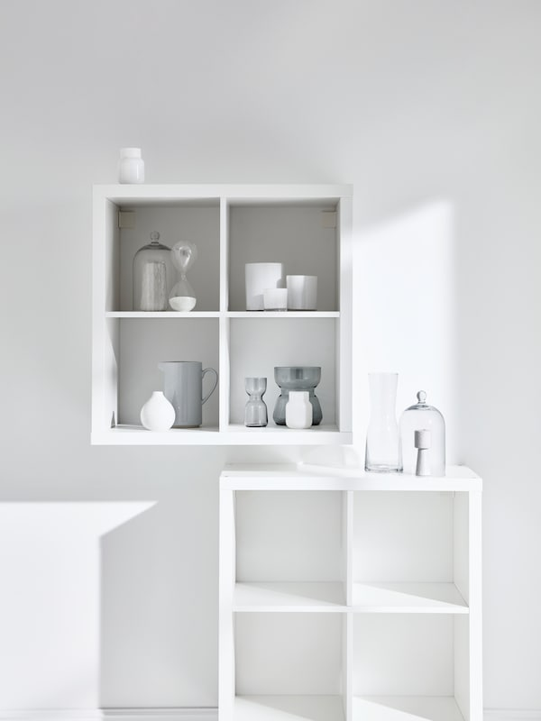 Two KALLAX shelving units with accessories on it.