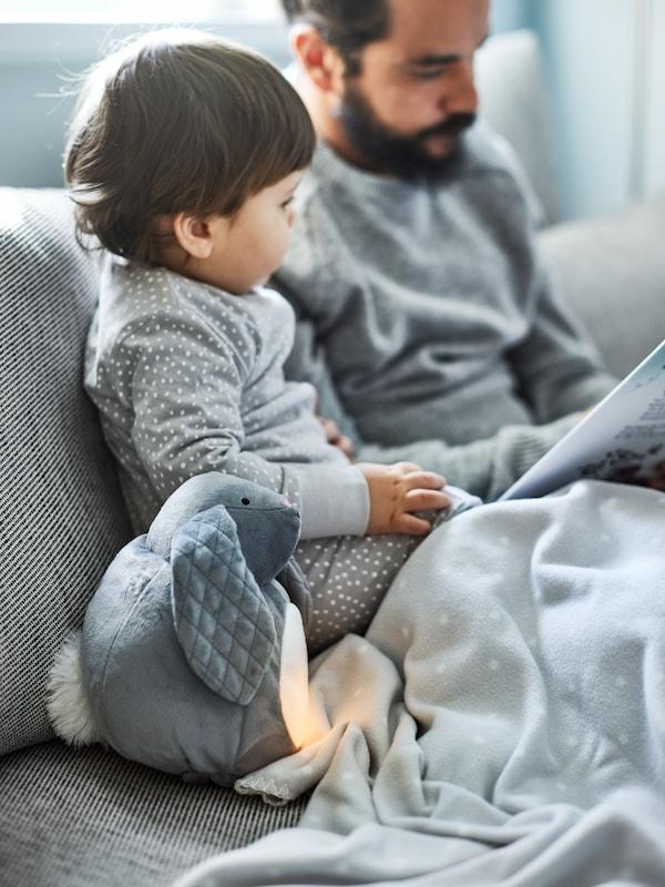 Une peluche grise PEKHULT, une veilleuse à DEL et une couverture LEN près d'un garçon et de son père en train de lire sur un canapé confortable.