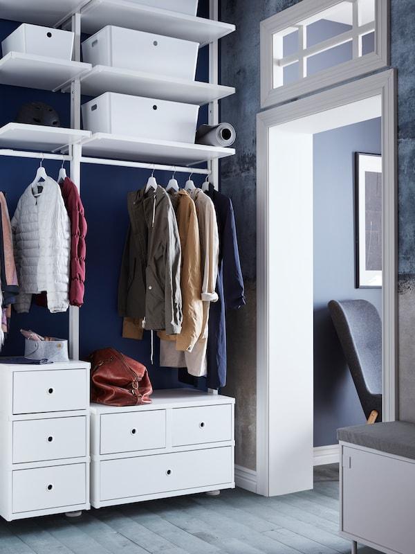 Un sistema de almacenaxe ELVARLI a carón dunha porta con dous mobles de caixóns, un colgadoiro e estantes con caixas KUGGIS.