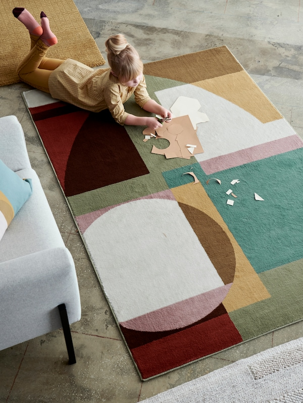 A girl with light colored hair lies on a colorful rug with an artistic design in front of an armchair with cushion.