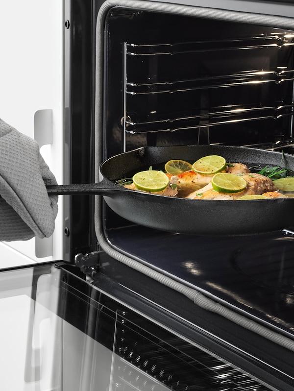 Ruka s kuhinjskom rukavicom stavlja VARDAGEN tavu za prženje od lijevanog željeza s ribom, limetom i začinskim biljem u pećnicu.