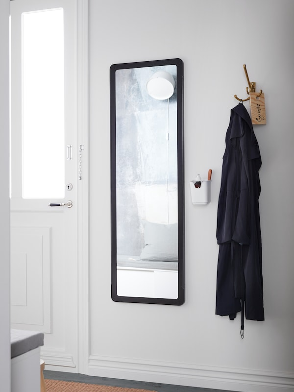 A long GRUA mirror with a black frame between a white door and a three-armed hook that has a coat hanging on it.