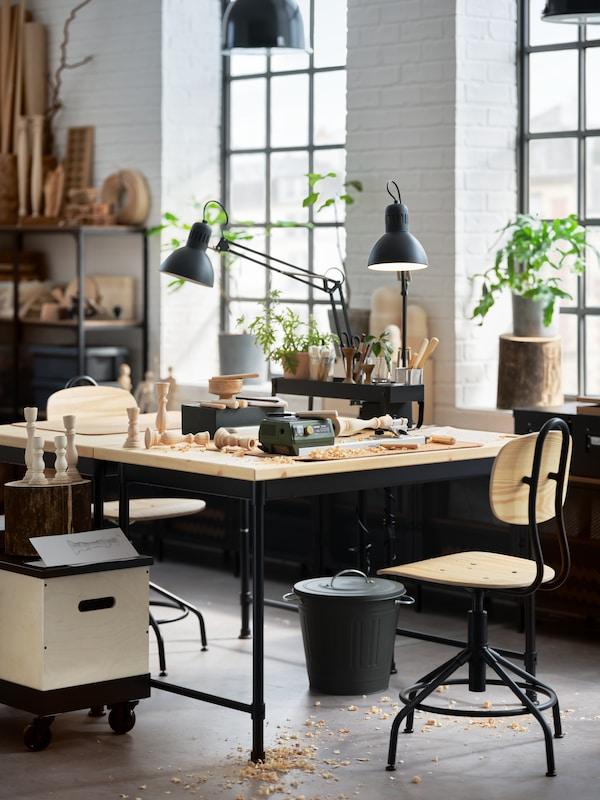 مكتبانخشب الصنوبر وكرسيان دوارانصنوبر/أسود ومصباحيعمل رمادي داكن ونوافذ كبيرة ونباتات في أواني.