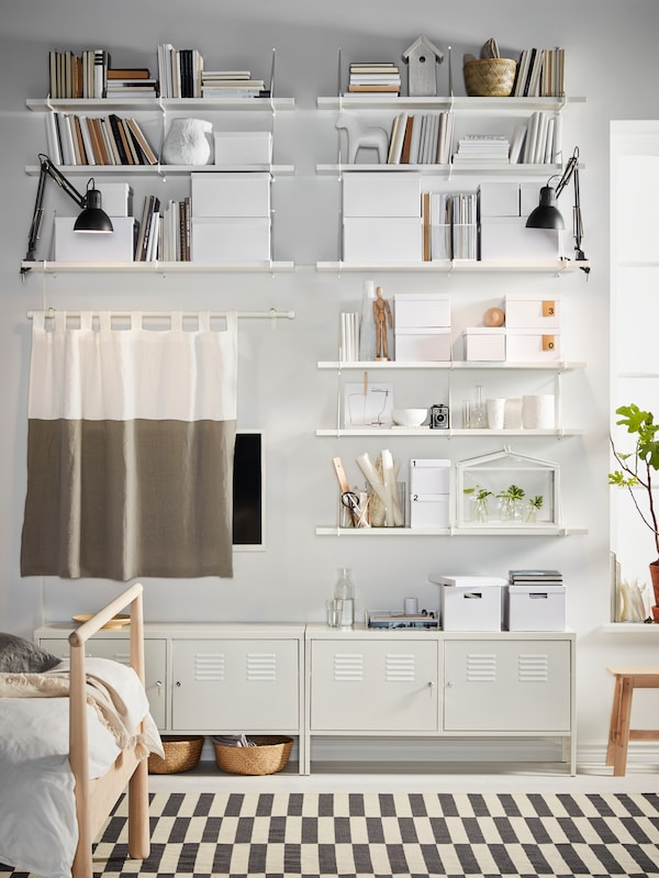 A wall with BERGSHULT/PERSHULT wall shelf combinations full of books and boxes, a curtain hiding a TV and two cabinets below.