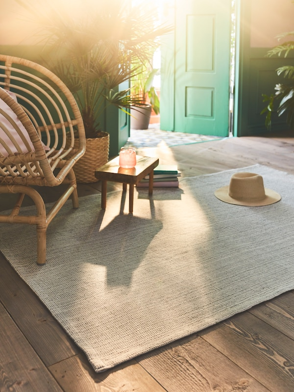 The flatwoven TIPHEDE rug in a natural/off-white colour placed on a wooden floor in a sunny room.