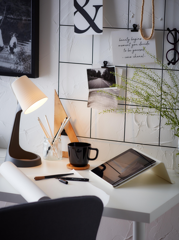 Nasuprot bijelog zida stoji bijeli radni stol s tamnosivom SVALLET lampom, ISBERGET stalkom za tablet, kavom i biljkom.