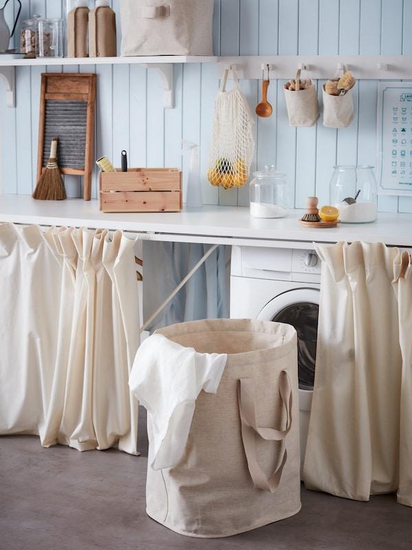Panier à linge de couleur crème devant une laveuse.