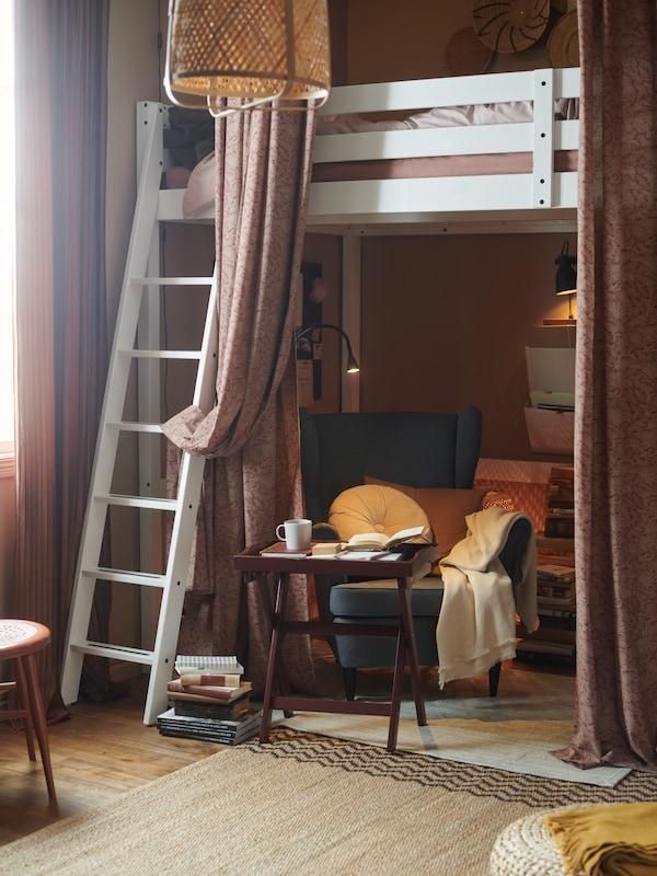 Valkoinen parvisänky, jonka alapuolella on kodikas lukunurkkaus, nojatuoli, tarjotinpöytä, pehmeät tekstiilit ja tunnelmavalaistus.