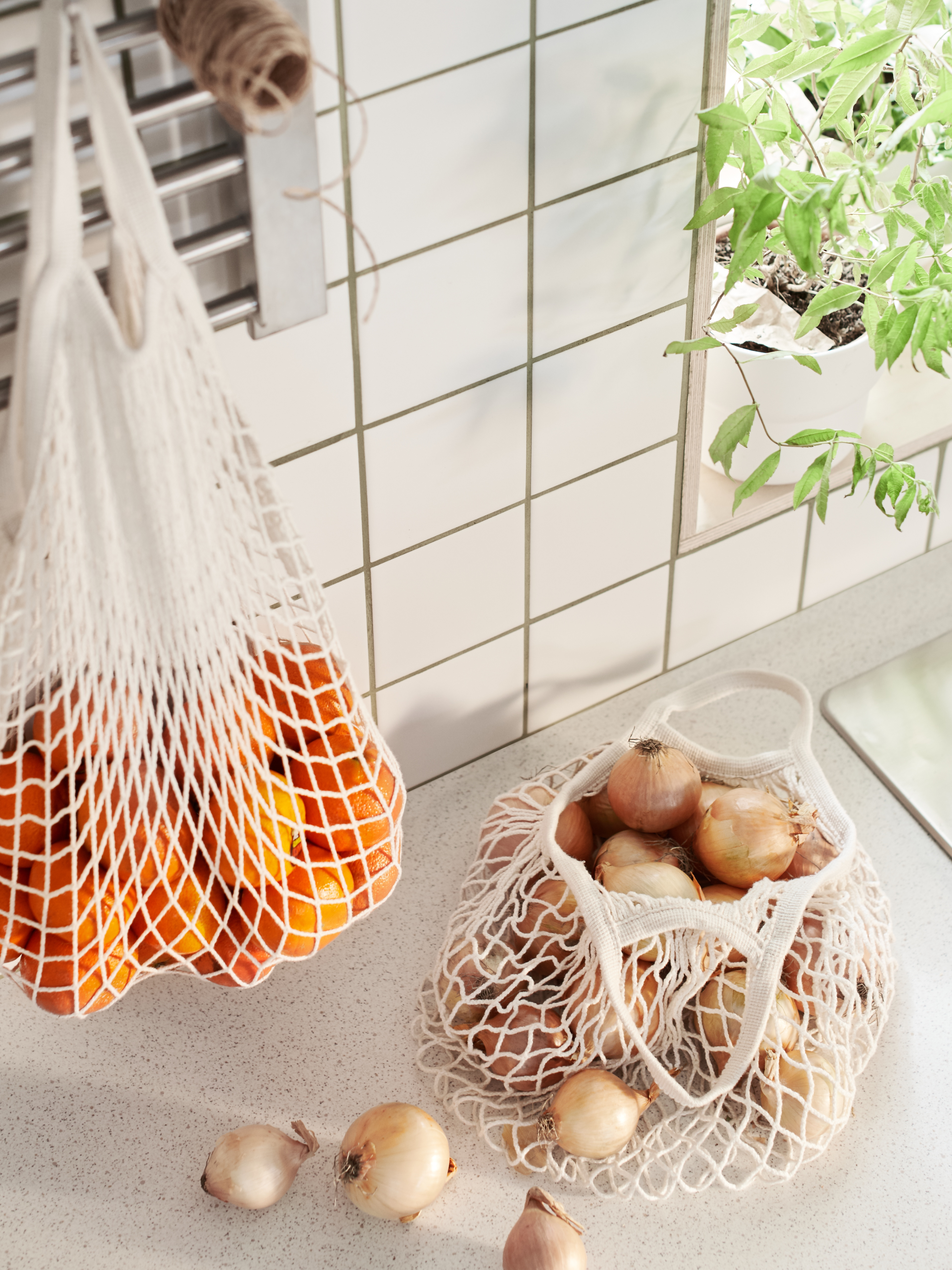 A kitchen top with a natural KUNGSFORS cotton net bag with onions. A wall grid holding a net bag with mandarins.