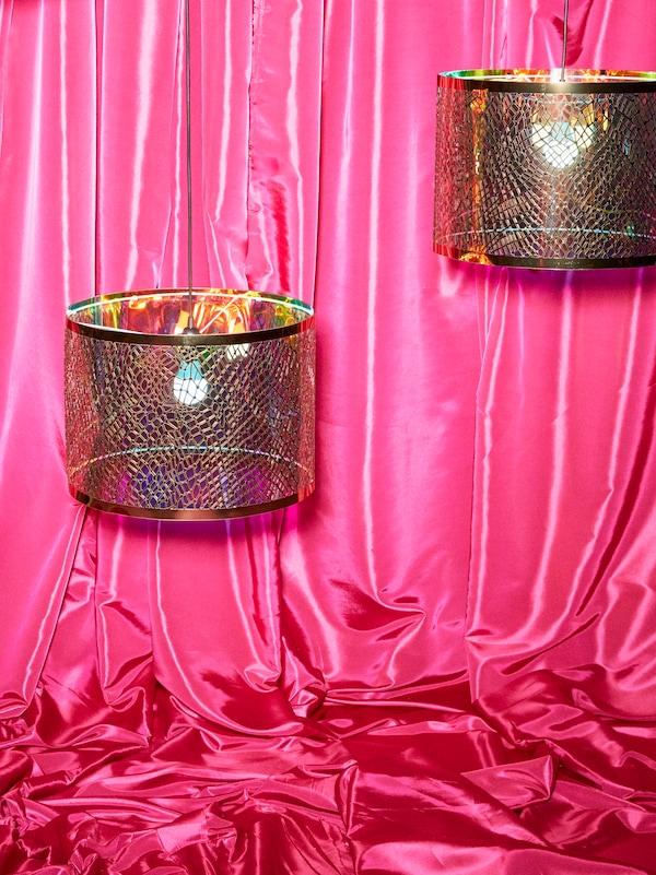Zwei KARISMATISK Leuchtenschirme mit goldfarbenem Netzmuster hängen vor einem Satinstoff in Rosa.