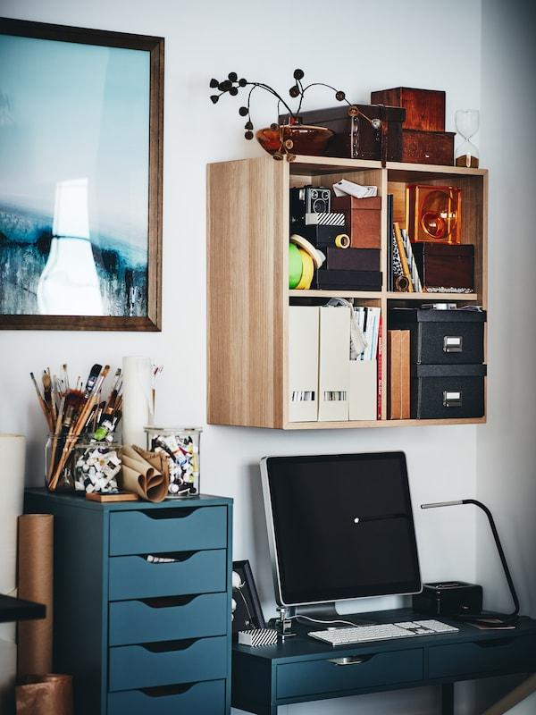 Ordinateur sur bureau ALEX en gris-turquoise, près d'un bloc-tiroirs ALEX, sous un élément mural EKET.