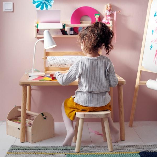 Dítě sedí na dětské stoličce FLISAT u dětského stolu FLISAT. Na stole je barevný papír a lampa.